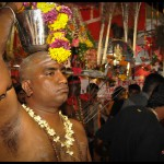 Devotee carrying a milk pot (pal kudam) with flowers